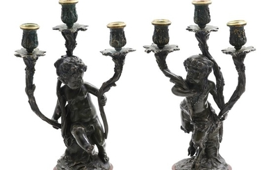 A pair of late 19th century patinated bronze candelabras in the shape of a putto and a faun, reddish marble bases. H. 43 cm. (2)