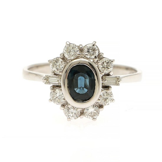 A sapphire and diamond ring set with an oval-cut sapphire encircled by eight brilliant-cut and two baguette-cut diamonds, mounted in 18k white gold. Size 59.