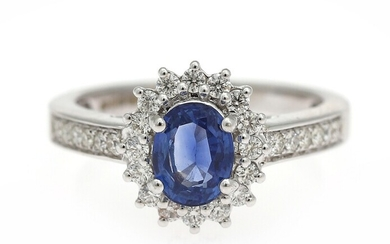 NOT SOLD. A sapphire and diamond ring set with an oval-cut sapphire encircled by numerous...