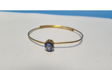AN UNMARKED YELLOW METAL BANGLE SET WITH POSSIBLY A SAPPHIRE...