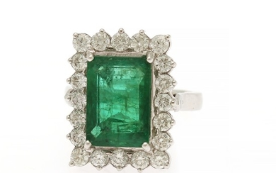 An emerald and diamond ring set with an emerald weighing app. 7.25 ct. encircled by numerous diamonds, mounted in 18k white gold. Size 56.