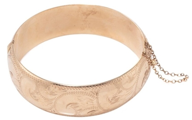 A 9CT GOLD ENGRAVED HINGED BAGLE; 19mm wide hollow bangle with scrolling engraving and safety chain, internal circ. 18cm, wt. 30.98g.