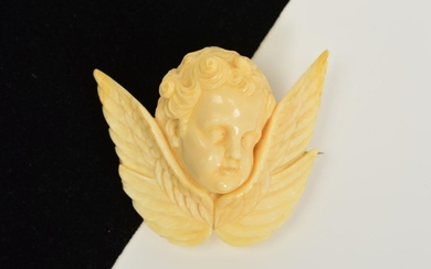 A MID VICTORIAN CARVED IVORY CHERUB BROOCH, carved in relief...