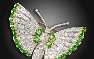 A demantoid garnet and diamond butterfly brooch, pave-set with graduated circular-cut diamonds, with garnet eyes, clusters of garnets and outer border of circular-cut garnets to the wings in gold, mounted 'en tremblant', diamonds approximately 16.00cts...