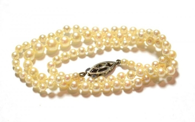 A graduated cultured pearl necklace, clasp stamped '9' and '.375',...