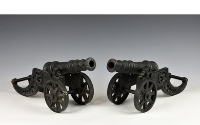 A pair of heavy cast metal fireside cannons, black painted o...