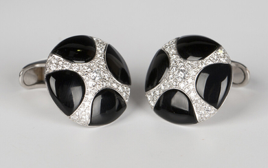 A pair of white gold, black onyx and diamond dress cufflinks, each circular front with a curved cruc