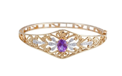 AN AMETHYST AND DIAMOND SET BANGLE, the oval amethyst to a g...