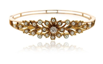 An Edwardian seed pearl and diamond bangle, of laurel design in yellow gold, 5.7cm inner diameter