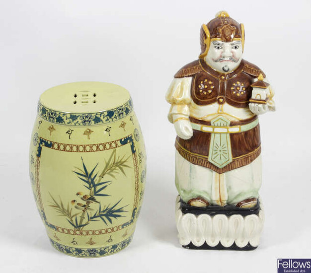 An Oriental pottery garden seat of pierced barrel form, together with a large pottery figure.