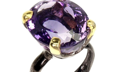 An amethyst ring set with an oval-cut amethyst, mounted in black rhodium and gold plated sterling silver. 19×12 mm. Size 58.