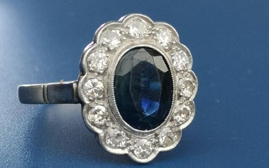 An oval sapphire & diamond millegrain set cluster ring,...