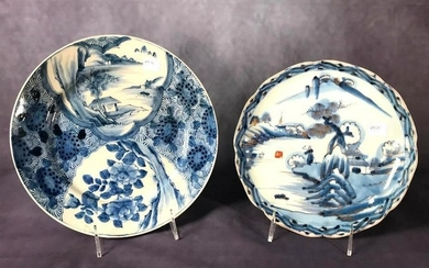 Larger blue and white dish decorated with a rustic dwelling on a river and floral lappets, signed with six character mark, together with a scalloped dish with a figure in a river landscape. 10 in. d. 8.5 in. d. Condition: Very good condition.