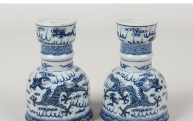 A pair of Chinese blue and white candle stands. Painted in u...
