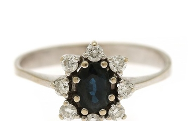 A sapphire and diamond cluster ring set with an oval-cut sapphire encircled by numerous brilliant-cut diamonds, mounted in 14k white gold. Size 55.5.