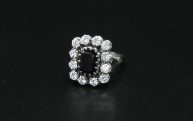 Daisy ring in white gold and platinum set with an emerald cut blue stone surrounded by 12 diamonds of about 0.2 ct - Gross weight: 10.31 g / tdd 55 (grindings)