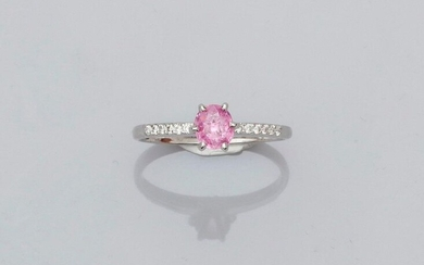 Solitaire ring in white gold, 750 MM, set with an oval pink sapphire weighing 0.61 carat between two lines of diamonds, size: 53, weight: 2.35gr. rough.