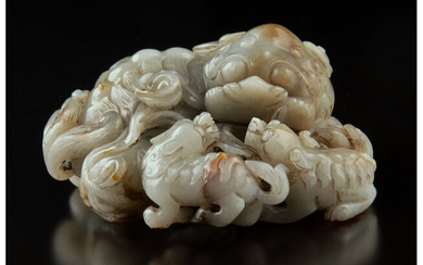 A Chinese Carved Celadon and Russet Jade Lion Toggle