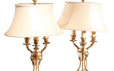 A PAIR OF FRENCH ORMOLU AND WHITE MARBLE TABLE LAMPS IN LOUIS XVI STYLE LATE 19TH CENTURY in the form of atheniennes, with three lights, with fluted urn nozzles and petal drip-pans, on hoof feet and a triform base, with shades and wired for electricity...
