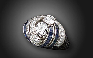 A sapphire and diamond cluster ring, Monture Cartier, set with three round brilliant-cut diamonds weighing approximately 0.57, 1.01 and 0.57cts, within a surround of calibre-cut sapphires and round brilliant-cut diamonds on a wirework band in platinum...