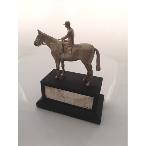 A sterling silver equestrian trophie. London 1983. On an ebo...