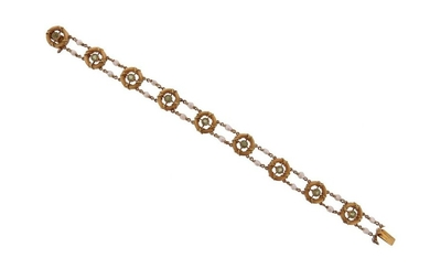An early 20th century peridot and seed pearl gold bracelet, the fluted circular links centred with old circular-cut peridots, with seed pearl spacers in gold, 18cm long