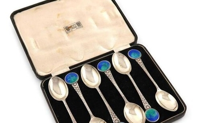 By W. H. Haseler for Liberty, a set of six silver and enamel teaspoons, Birmingham 1914, the tapering stems with chased decoration and with blue / green enamel circular finials, in a fitted case, the inside of the cover with ~Liberty Regent Street...