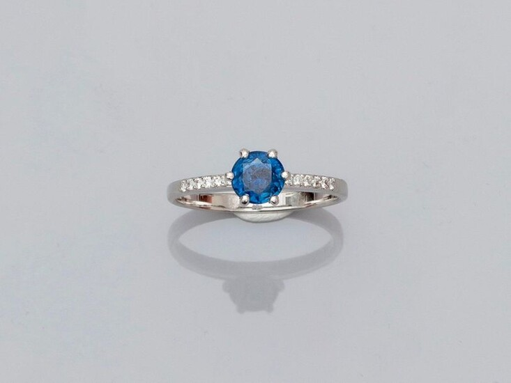 Solitaire ring in white gold, 750 MM, set with a round sapphire weighing about 1 carat between two lines of brilliants, size: 54, weight: 2.6gr. gross.