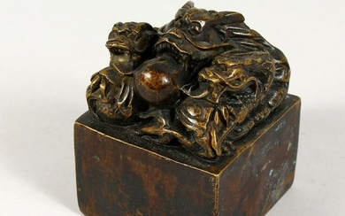A SQUARE BRONZE SEAL, mounted with dragons. 3ins wide.