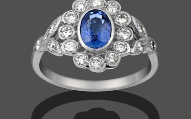 A Sapphire and Diamond Cluster Ring, the oval cut sapphire...