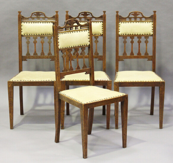 A set of four Edwardian Arts and Crafts oak framed dining chairs with pierced top rails and stylized
