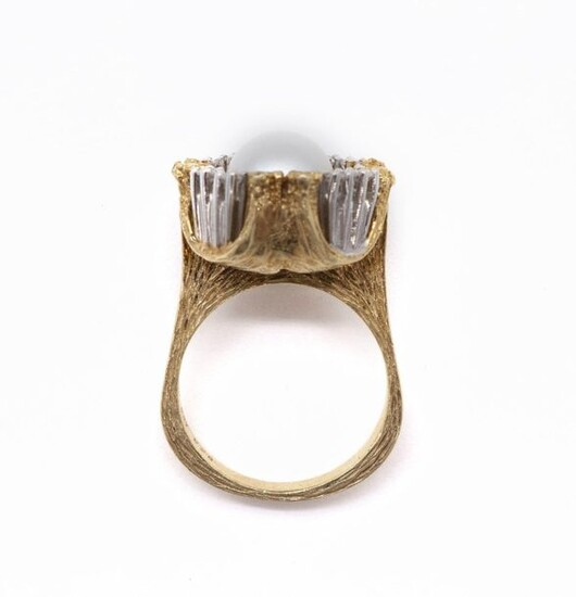 RING in 14K yellow and white gold retaining in its center a white pearl (untested) in a setting of six brilliant-cut diamonds. Set in chased gold. TDD: 55. Gross weight: 10.54 gr. A diamond, pearl and gold ring.