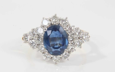 Sapphire and diamond cluster ring with an oval mixed cut blue sapphire measuring approximately 9.5mm x 7.7mm x 3.3mm surrounded by twelve brilliant cut diamonds with a further six diamonds to the s...