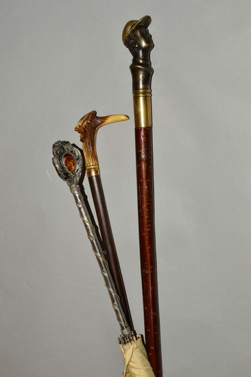 TWO DECORATIVE HANDLED WALKING STICKS AND AN UMBRELLA, one w...