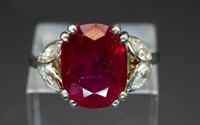 A RUBY AND DIAMOND RING, the oval cut ruby set between