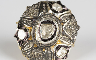 A gilt metal and diamond ring, probably Indian, of large oval panel shaped form, mounted with four p