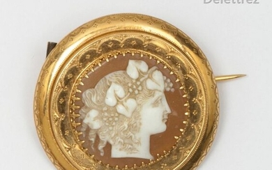 Chiseled yellow gold brooch, adorned with a shell cameo representing the profile of a woman with hair decorated with vine branches. Diameter: 3.2cm. Gross weight: 5g.