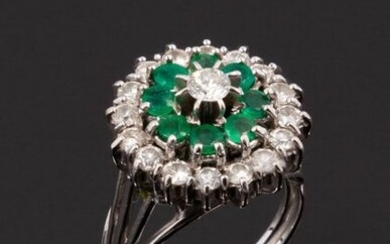 Daisy ring in 18k (750 thousandths) white gold with an outer surround of round diamonds, then round emeralds and in the center a round diamond (fissure). Work from the 1950s.