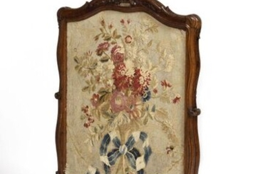 """Moulded and carved walnut mantel screen decorated with flowers and foliage, resting on a scrolled base, adorned with a dotted tapestry sliding leaf, inscribed in ink on the reverse: """"Cadir bleu"""" (blue frame). Louis XV period. H : 101 cm, L : 65 cm..."""