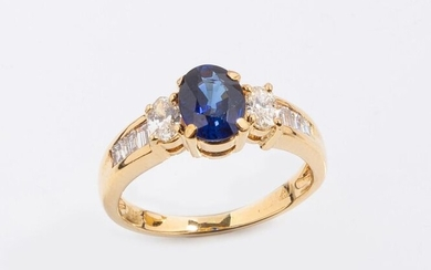 Ring in 18k (750 thousandths) yellow gold set with a beautiful oval natural royal blue sapphire (slight wear of the edges) surrounded by two oval diamonds and decorated with diamond baguettes on the shoulders.