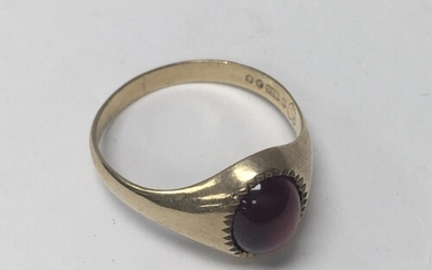 A 9ct gold gents ring set with a cabochon garnet. (W). 3.4g