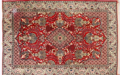 A PERSIAN ISFAHAN CARPET, red ground with central