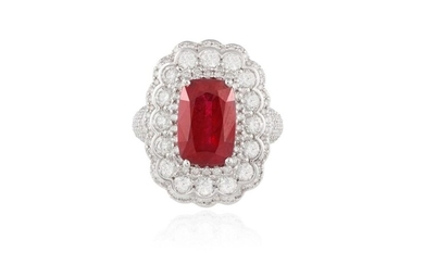 A RUBY AND DIAMOND DRESS RING The elongated cushion-shaped ruby weighing 4.03cts, within a four-claw setting and a round brilliant-cut diamond surround to similarly-cut diamond shoulders, mounted in 18K gold, diamonds approximately 2.50cts total...