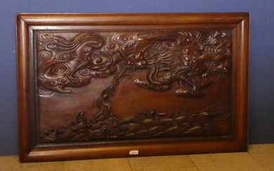 A framed wood panel decorated with a dragon and fish carving...