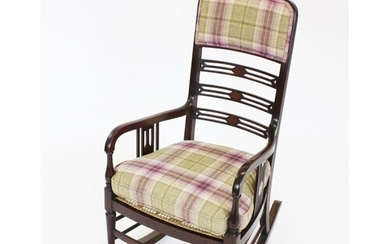 An Edwardian mahogany rocking chair, with a padded back rest...