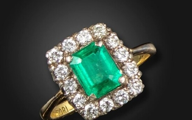 An emerald and diamond cluster ring, the emerald-cut emerald is set within a surround of round brilliant-cut diamonds in platinum and gold, size P, case