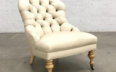 An upholstered tufted slipper chair