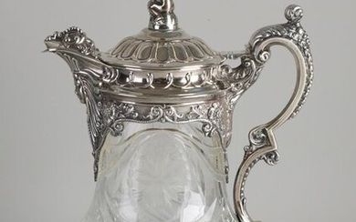 Beautiful pitcher with silver mounts, 835/000. Large jug decorated with cut work with floral decoration, placed on a round silver base with lambrequins, cable edge and fluting. The jug has a silver frame with spout and handle with volutes, floral...