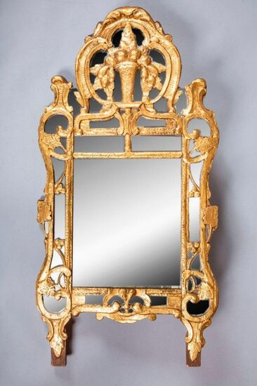 Carved and gilded wood mirror, the pediment decorated...