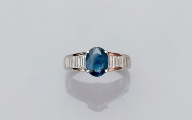 White gold ring, 750 MM, set with an oval sapphire weighing 2.01 carats between two lines of baguette-cut diamonds, total about 1 carat, size: 54, weight: 6.6gr. rough.